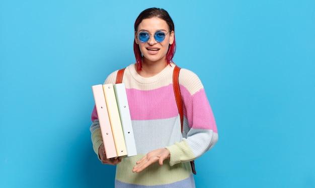 Jonge aantrekkelijke roodharige vrouw die vrolijk glimlacht, zich gelukkig voelt en een concept in exemplaarruimte met handpalm toont. universiteitsstudent concept
