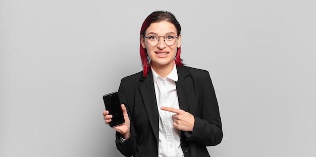 Jonge aantrekkelijke roodharige vrouw die vrolijk glimlacht, zich gelukkig voelt en naar de zijkant en naar boven wijst, voorwerp in exemplaarruimte toont. bedrijfsconcept