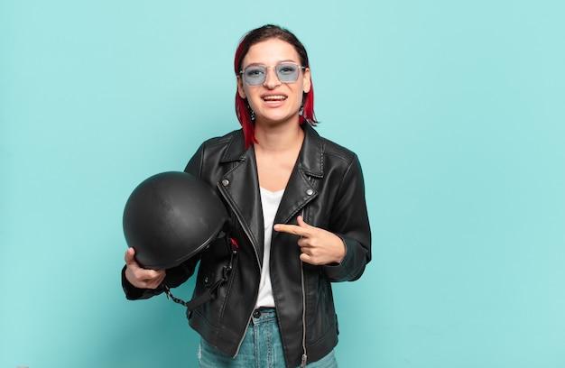 Jonge aantrekkelijke roodharige vrouw die vrolijk glimlacht, zich gelukkig voelt en naar de zijkant en naar boven wijst, voorwerp in exemplaarruimte toont. motorrijder concept
