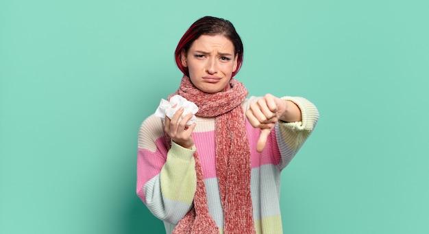 Jonge aantrekkelijke roodharige vrouw die zich boos, boos, geïrriteerd, teleurgesteld of ontevreden voelt, duimen naar beneden laat zien met een ernstig blikgriepconcept