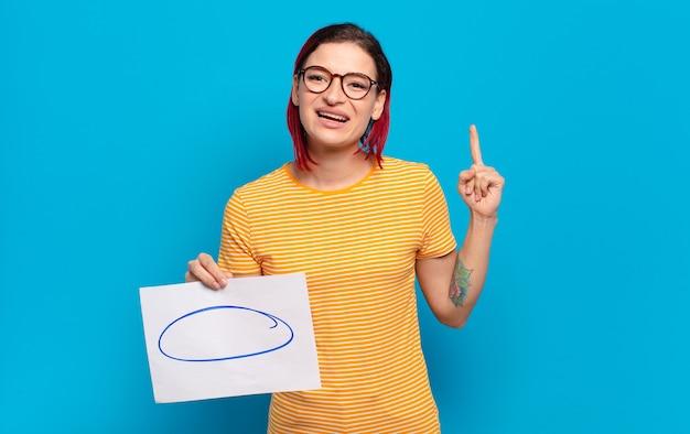 Jonge aantrekkelijke roodharige vrouw die zich een gelukkig en opgewonden genie voelt na het realiseren van een idee, vrolijk de vinger opstekend, eureka!