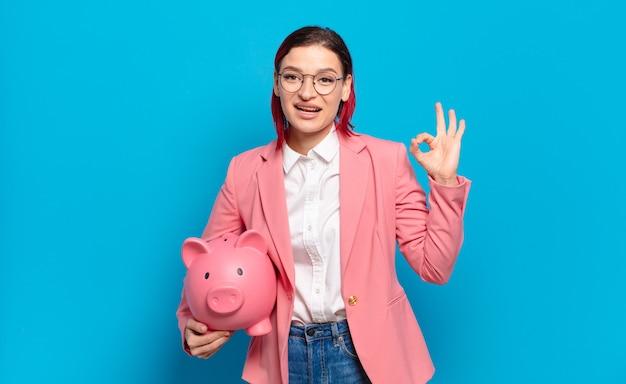 Jonge aantrekkelijke roodharige vrouw die zich gelukkig, ontspannen en tevreden voelt, goedkeuring toont met een goed gebaar, glimlachend. humoristisch bedrijfsconcept.