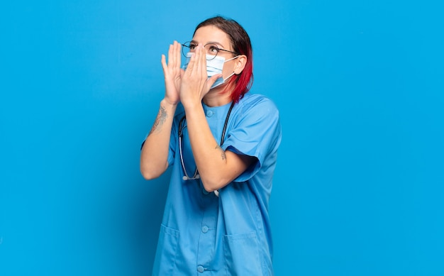 Jonge aantrekkelijke roodharige vrouw die zich gelukkig, opgewonden en positief voelt, een grote schreeuw geeft met de handen naast de mond, roept. ziekenhuis verpleegkundige concept