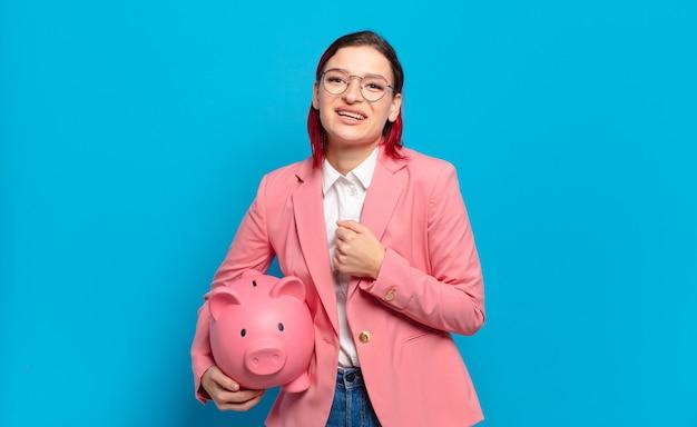 Jonge aantrekkelijke roodharige vrouw die zich gelukkig, positief en succesvol voelt, gemotiveerd wanneer ze voor een uitdaging staat of goede resultaten viert. humoristisch bedrijfsconcept.