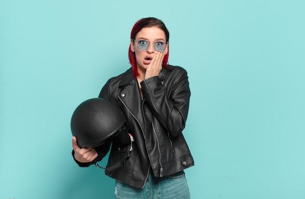 Jonge aantrekkelijke roodharige vrouw die zich geschokt en bang voelt, doodsbang kijkt met open mond en handen op de wangen. motorrijder concept