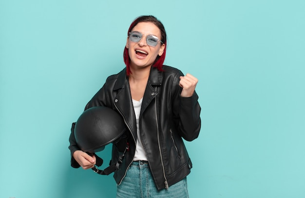 Jonge aantrekkelijke roodharige vrouw die zich geschokt, opgewonden en gelukkig voelt, lacht en succes viert, en zegt wow!. motorrijder concept