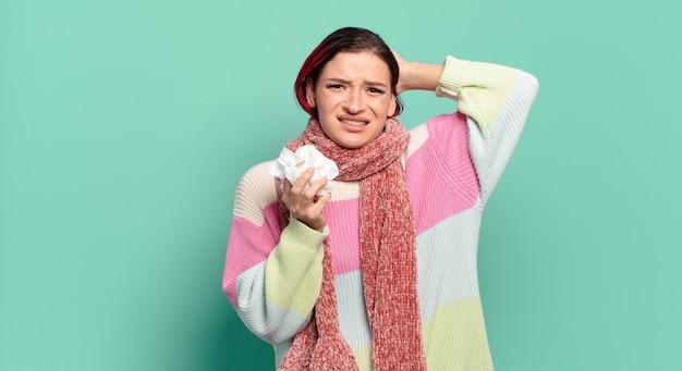 Jonge aantrekkelijke roodharige vrouw die zich gestrest, bezorgd, angstig of bang voelt, met de handen op het hoofd, in paniek raakt bij het concept van de foutgriep