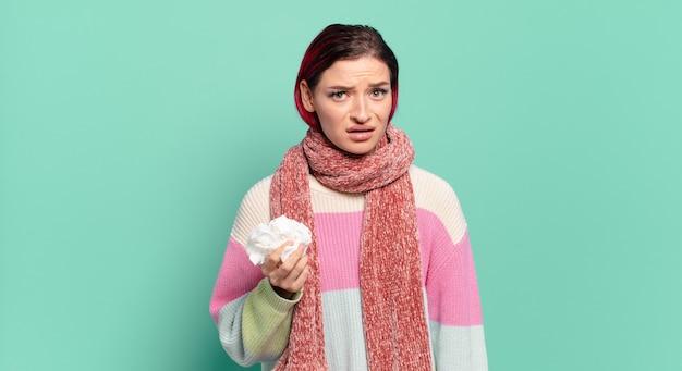 Jonge aantrekkelijke roodharige vrouw die zich verbaasd en verward voelt, met een stomme, verbijsterde uitdrukking die naar iets onverwachts griepconcept kijkt