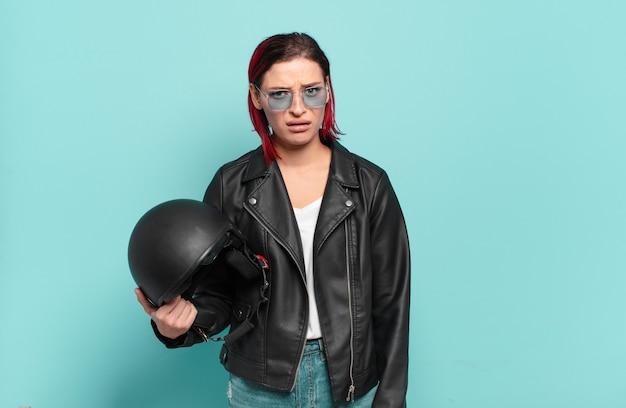 Jonge aantrekkelijke roodharige vrouw die zich verbaasd en verward voelt, met een stomme, verbijsterde uitdrukking die naar iets onverwachts kijkt. motorrijder concept