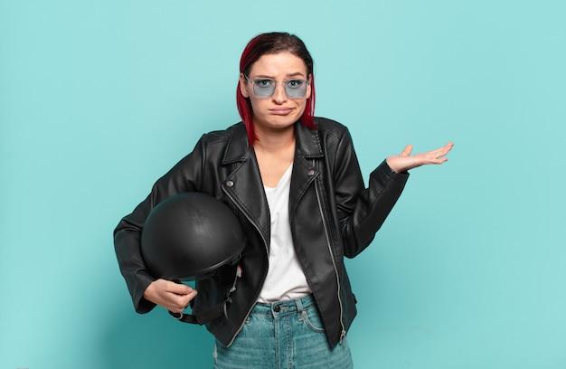Jonge aantrekkelijke roodharige vrouw die zich verbaasd en verward voelt, twijfelt, weegt of verschillende opties kiest met een grappige uitdrukking. motorrijder concept