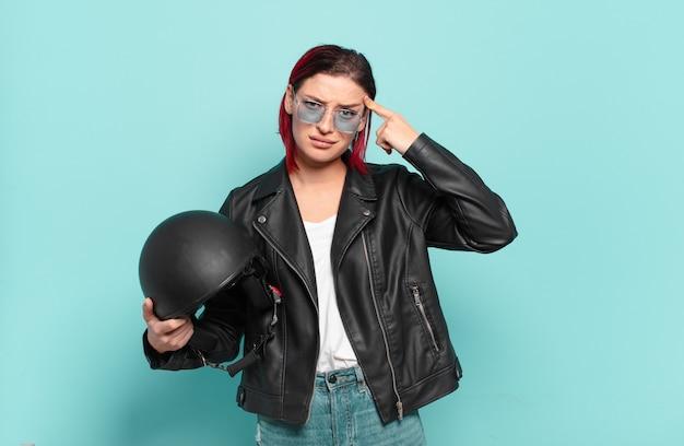 Jonge aantrekkelijke roodharige vrouw die zich verward en verbaasd voelt en laat zien dat je gek, gek of gek bent. motorrijder concept