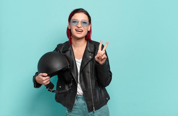 Jonge aantrekkelijke roodharige vrouw lacht en ziet er gelukkig, zorgeloos en positief uit, gebarend overwinning of vrede met één hand