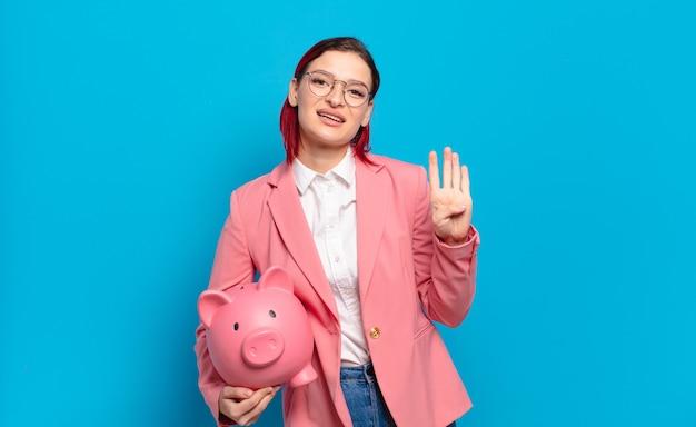 Jonge aantrekkelijke roodharige vrouw lacht en ziet er vriendelijk uit, nummer vier of vierde met hand naar voren, aftellend. humoristisch bedrijfsconcept.