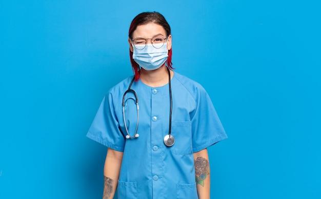 Jonge aantrekkelijke roodharige vrouw met vrolijke, zorgeloze, rebelse houding, grappen maken en tong uitsteken, plezier maken. ziekenhuis verpleegster concept