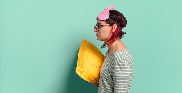 Jonge aantrekkelijke roodharige vrouw op profielweergave die ruimte vooruit wil kopiëren, denkt, zich voorstelt of dagdroomt en pyjama draagt