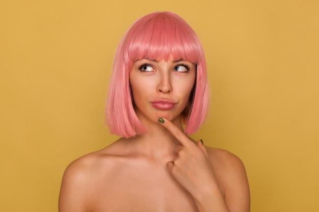 Jonge aantrekkelijke roze harige vrouw met bob kapsel peinzend naar boven kijkend met gevouwen lippen, wijsvinger op haar kin terwijl ze over mosterdmuur staat
