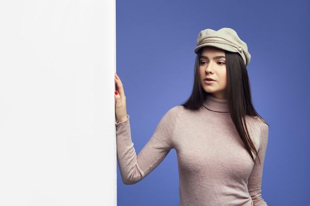 Jonge aantrekkelijke schattige jonge vrouw die zich naast een lege witte aanplakbordmuur bevindt