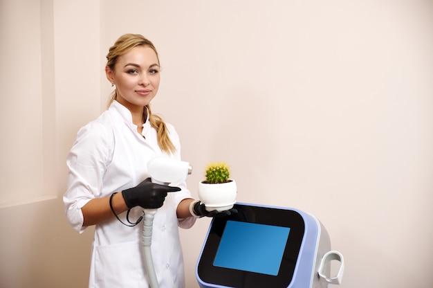 Jonge aantrekkelijke schoonheidsspecialiste schoonheidsspecialiste houdt een pot met cactus en staat in de buurt van een laserapparaat voor haarverwijdering