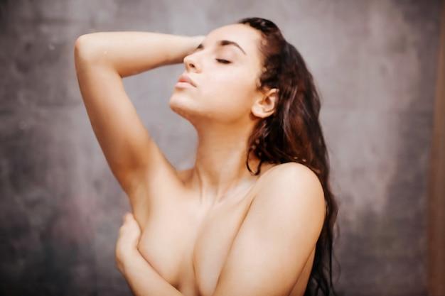 Jonge aantrekkelijke sexy vrouw in douche. poseren voor de camera. ogen dicht. naakt lichaam. model omslagborst met één hand. genot.