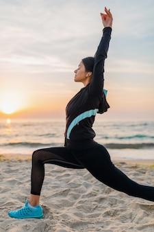 Jonge aantrekkelijke slanke vrouw die sportoefeningen doet op het strand van de ochtendzonsopgang in sportkleding, gezonde levensstijl, luisteren naar muziek op oortelefoons, waardoor rekken