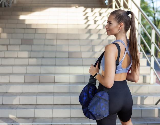 Jonge, aantrekkelijke, slanke vrouw in sportkleding die zich voorbereidt om te gaan trainen met een trainingstas en mat in de hand