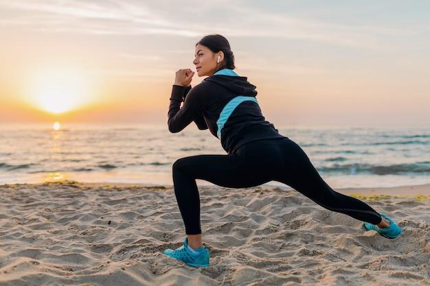 Jonge aantrekkelijke slanke vrouw sport oefeningen doen op ochtend zonsopgang strand in sportkleding, gezonde levensstijl, luisteren naar muziek op oortelefoons, waardoor strekken voor benen