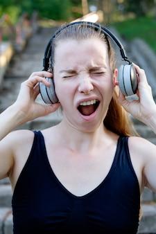 Jonge aantrekkelijke slaperige vrouw die aan te luide muziek luistert en vóór een ochtendjogging geeuwt. klaar om te rennen. gezonde sport levensstijl. fitness en training buiten.