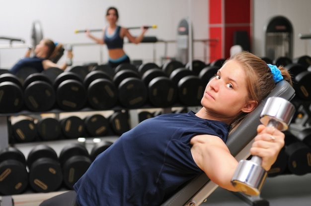 Jonge aantrekkelijke sport meisje in sportkleding op fitnessapparatuur training met halters op sportschool
