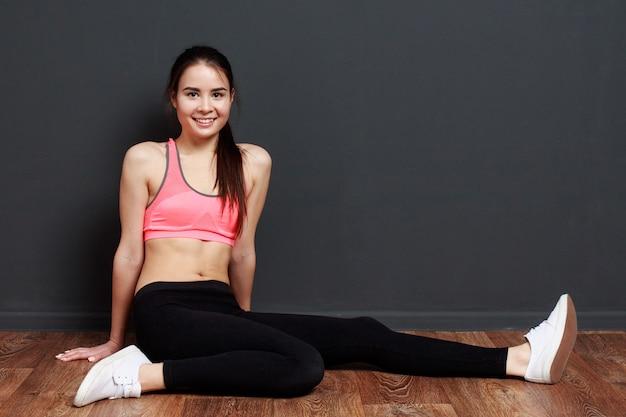 Jonge aantrekkelijke sportieve en vrouw die glimlacht rust