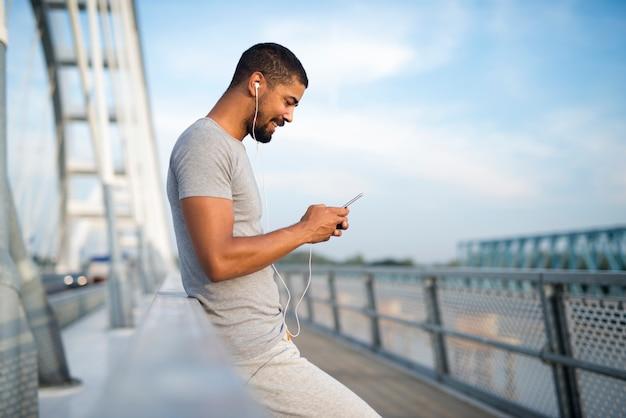 Jonge aantrekkelijke sportieve man met behulp van telefoon en lachend op de brug