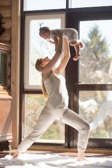 Jonge aantrekkelijke sportieve moeder die oefeningen met haar baby doet