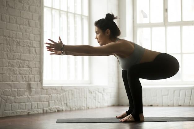 Jonge aantrekkelijke sportieve vrouw die oefeningen, witte zolderstudio doet