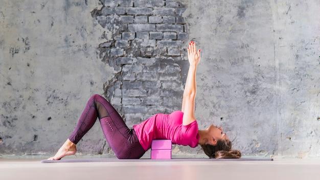 Jonge aantrekkelijke sportieve yogivrouw het praktizeren yoga die roze blok gebruiken