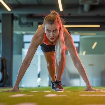 Jonge aantrekkelijke sportvrouw die voor marathon in gymnastiek voorbereidingen treft