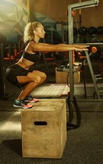 Jonge aantrekkelijke sportvrouw in sportkleding oefent springen op een houten kist in de sportschool. functioneel trainingsconcept