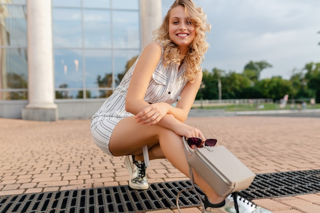 Jonge aantrekkelijke stijlvolle blonde vrouw zitten in stad straat in zomer mode stijl jurk dragen zonnebril, tas, silvers sneakers