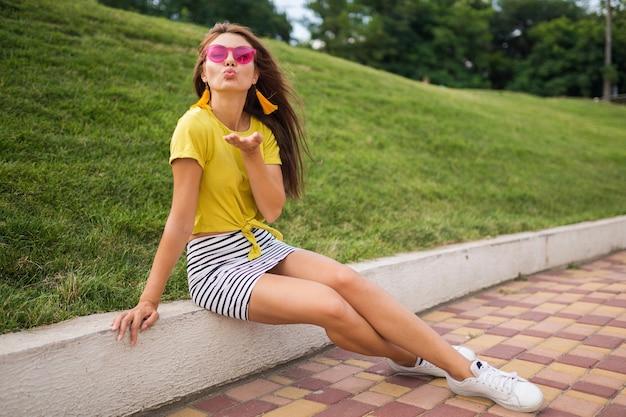 Jonge aantrekkelijke stijlvolle lachende vrouw met plezier in stadspark, gele top, gestreepte minirok, roze zonnebril, witte sneakers, zomer stijl modetrend, kus verzenden, flirten dragen