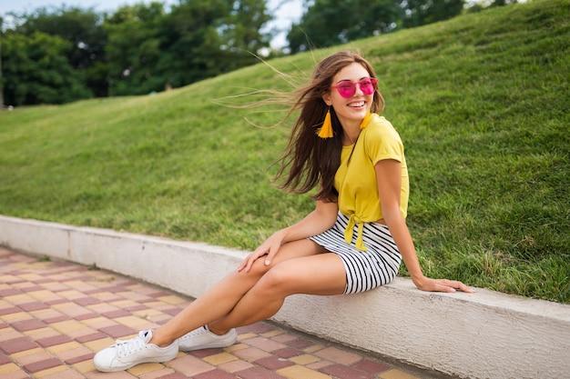 Jonge aantrekkelijke stijlvolle lachende vrouw met plezier in stadspark, positief, emotioneel, gele top, gestreepte minirok, roze zonnebril, witte sneakers, zomer stijl modetrend, lange benen dragen