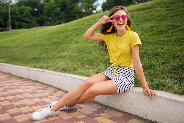 Jonge aantrekkelijke stijlvolle lachende vrouw met plezier in stadspark, positief, emotioneel, gele top, gestreepte minirok, roze zonnebril, witte sneakers, zomerstijl modetrend, vredesteken dragen
