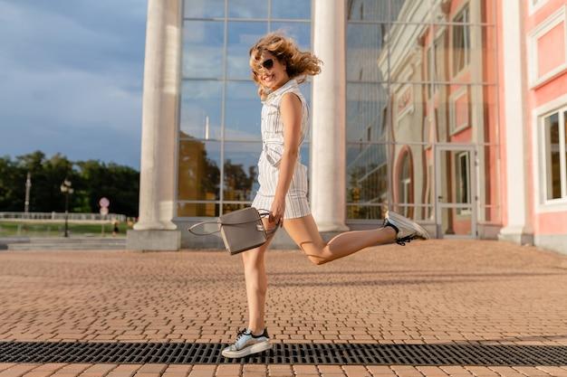 Jonge aantrekkelijke stijlvolle vrouw springen grappig uitgevoerd in sneakers in stad straat in zomer mode stijl witte jurk dragen van een zonnebril en handtas