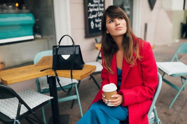 Jonge aantrekkelijke stijlvolle vrouw zitten in stad straat café in rode jas koffie drinken dragen blauwe jurk