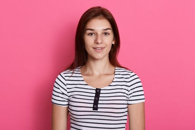 Jonge aantrekkelijke tiener die een gestreept casual t-shirt draagt, poseren tegen een roze muur, met een charmante glimlach, ziet er gelukkig uit.