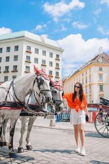 Jonge aantrekkelijke toerist in openlucht in italiaanse stad met paarden