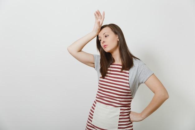Jonge aantrekkelijke verdrietig boos brunette kaukasische huisvrouw in gestreepte schort geïsoleerd. mooie huishoudstervrouw legde haar hand op haar hoofd en raakte ze aan