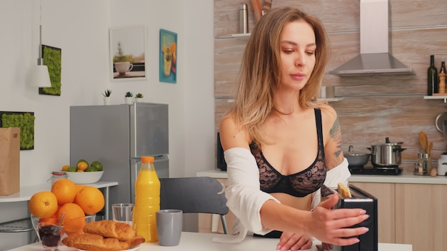 Jonge aantrekkelijke verleidelijke dame die 's ochtends in een gezellig interieur thuis zit en een heerlijk en gezond ontbijt bereidt. sexy mooie vrouw die geroosterd brood maakt gebruikend broodrooster die zwarte lingerie draagt.