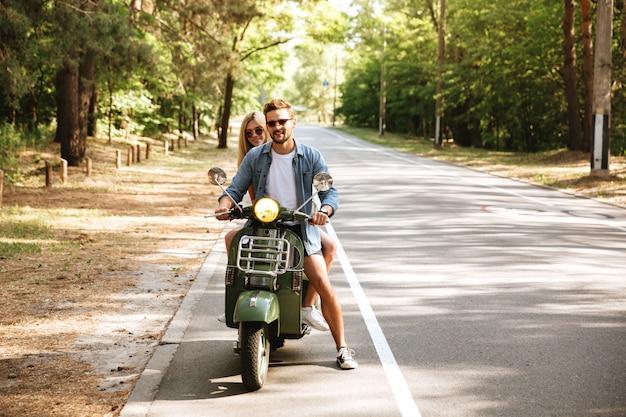 Jonge aantrekkelijke verliefde paar op scooter buitenshuis. opzij kijken.