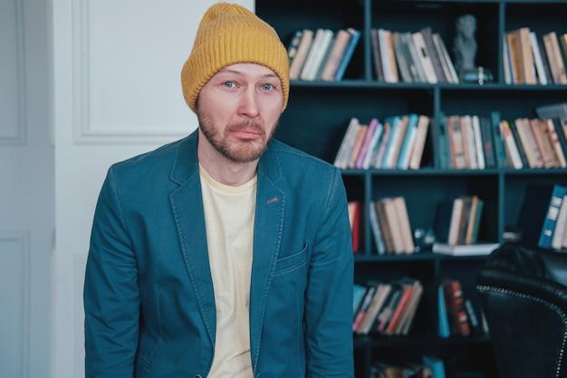 Jonge aantrekkelijke verraste mensen kinderverliezer hipster in gele hoed op blauwe muurbibliotheek