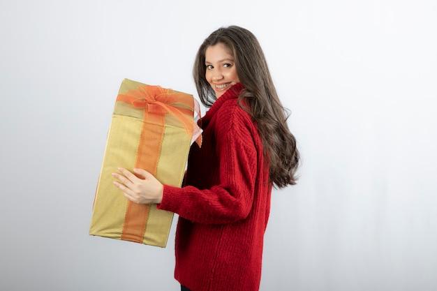 Jonge aantrekkelijke vrolijke vrouw met huidige kerstdoos.