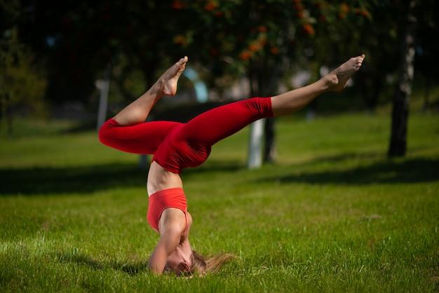 Jonge aantrekkelijke vrouw beoefenen van yoga buitenshuis, het meisje voert een handstand ondersteboven uit