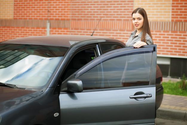 Jonge, aantrekkelijke vrouw besturen van een auto, naar huis gaan van het werk